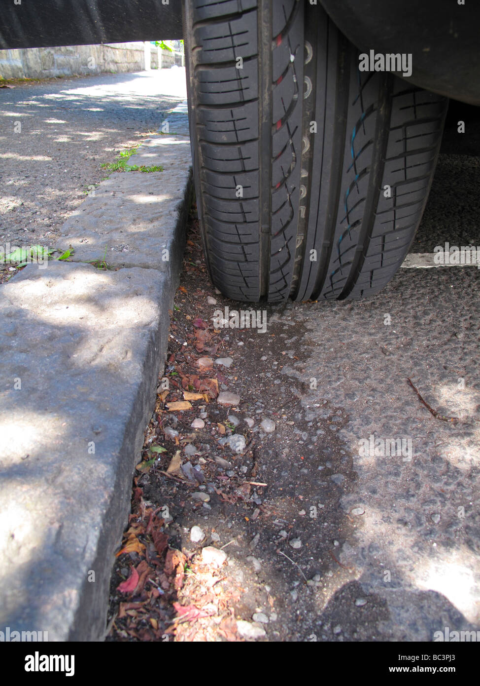 Parked car tyre at kerb - Stock Image