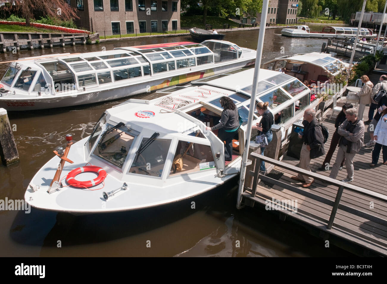 Passengers embarking a canal bus on an Amsterdam Canal - Stock Image