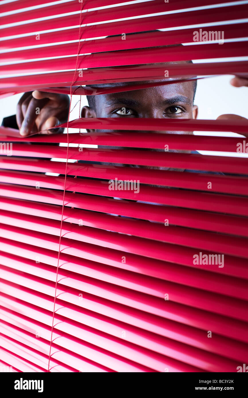 afro american businessman glancing through red blinds Copy space - Stock Image
