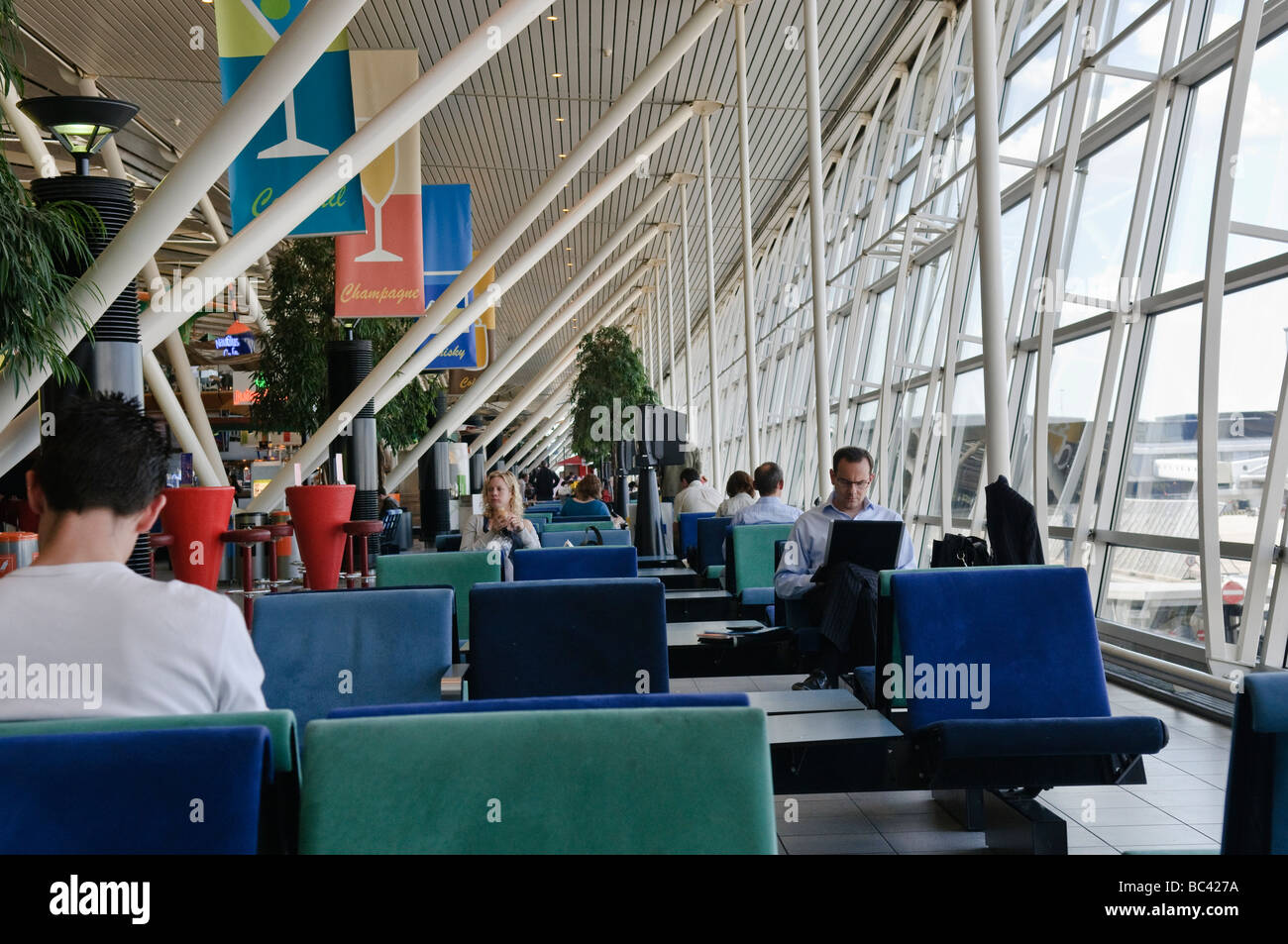 Passengers waiting at departure lounge at Schiphol Airport - Stock Image