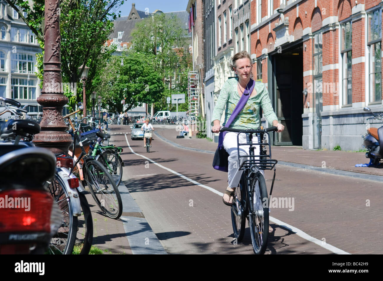 Lady cyclist on a street in Amsterdam - Stock Image