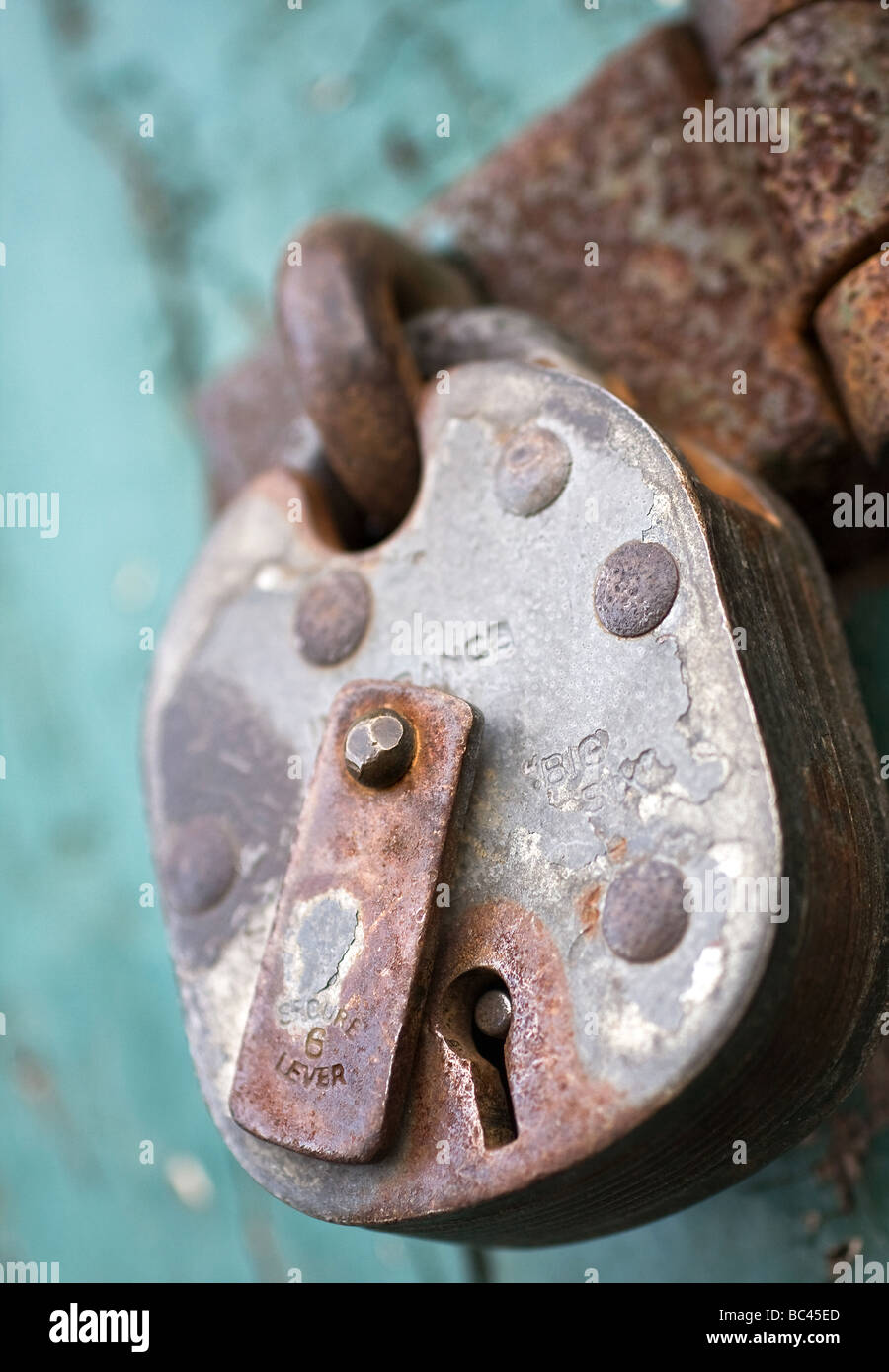 Close shot of a pad lock on a terquoice background. - Stock Image