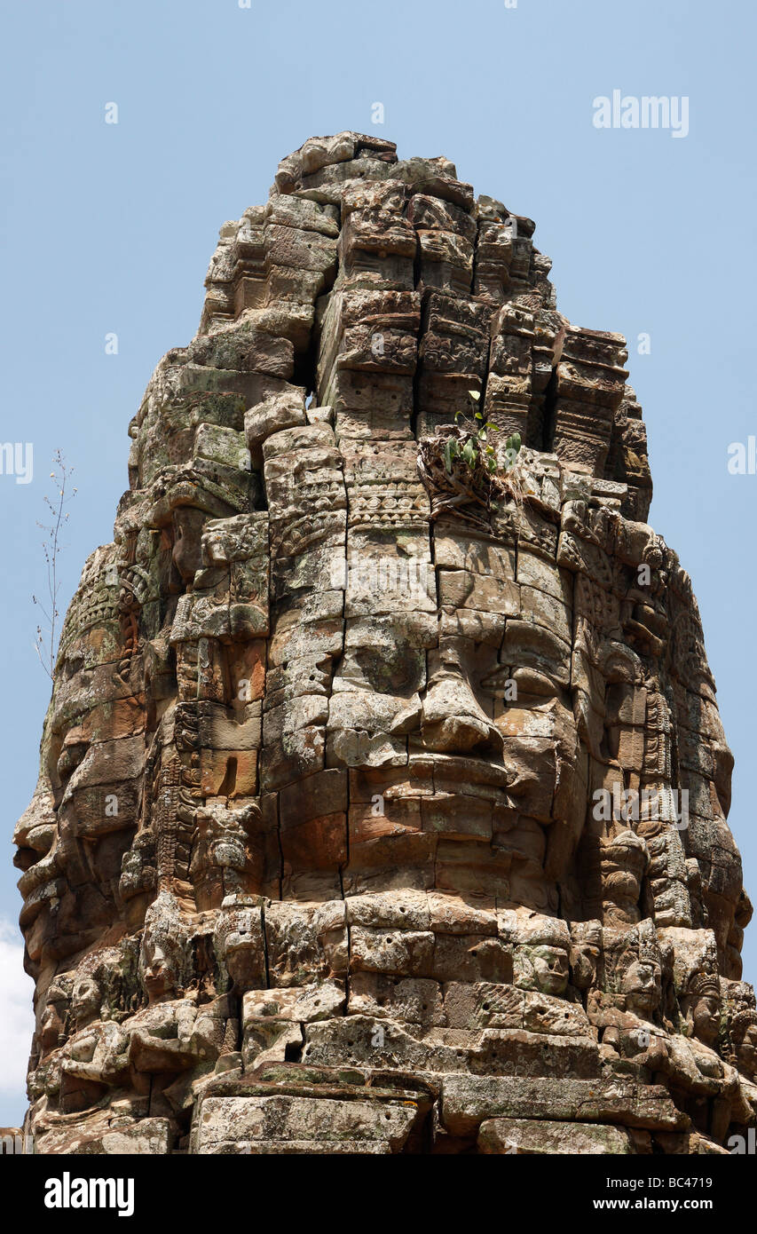 Buddha faces carved in stone tower, 'Ta Prohm' temple ruins, Angkor, Cambodia - Stock Image