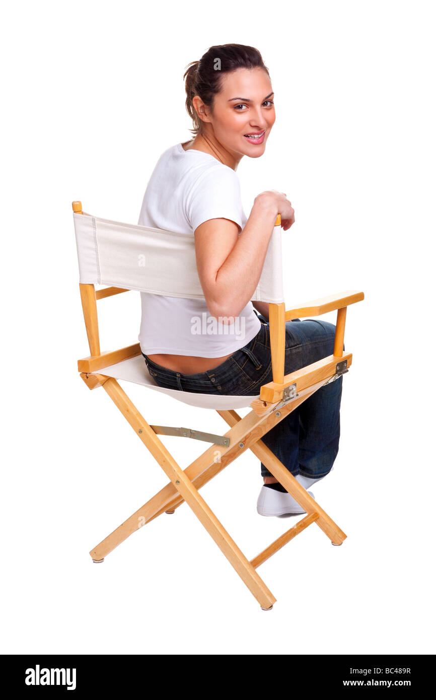 Brunette woman sat in a directors chair - Stock Image