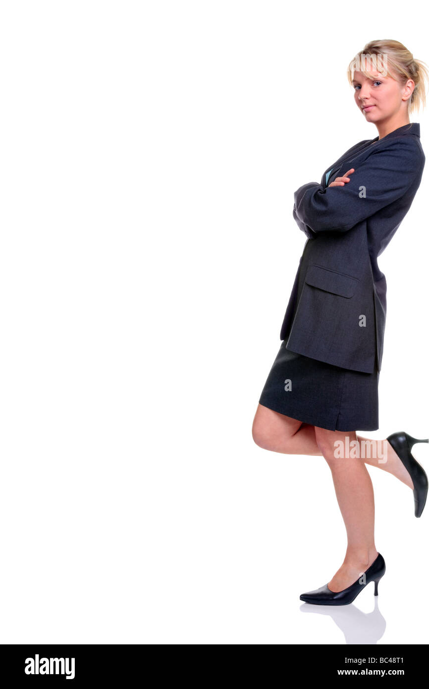 Blond businesswoman in suit standing leaning against something isolated on a white background - Stock Image