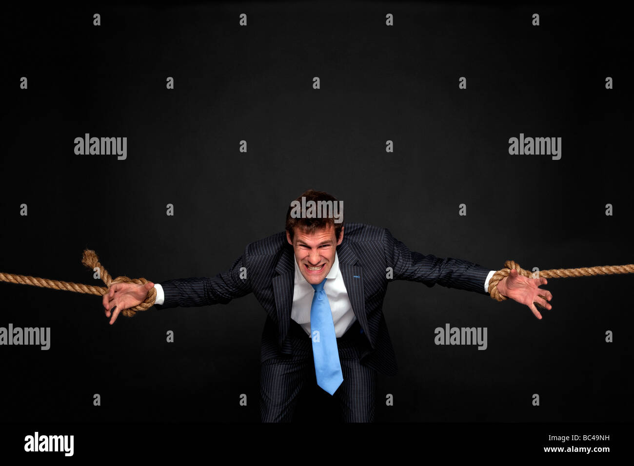 Businessman struggling as he s pulled by rope attached to his wrists on both sides dark background - Stock Image