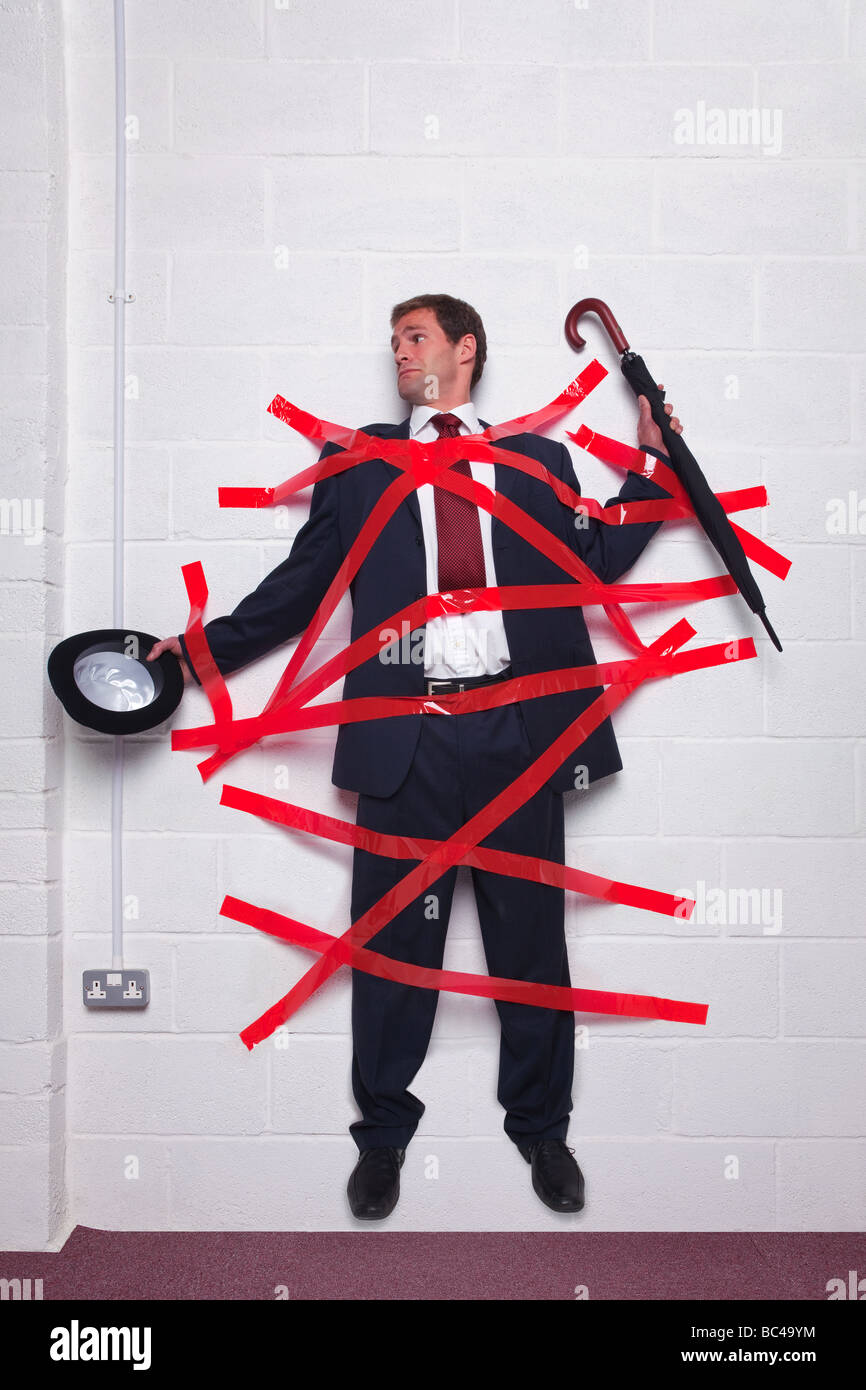 Businessman holding an umbrella and bowler hat stuck to a wall with red tape Stock Photo