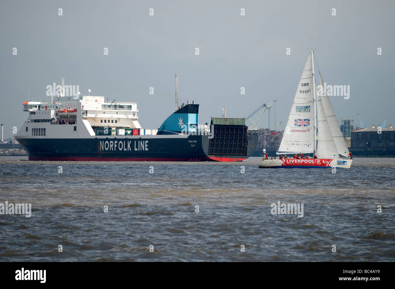 Clipper yacht Race Sailing boat next to Norfolk Line Ferry from Liverpool to Ireland on River Mersey - Stock Image