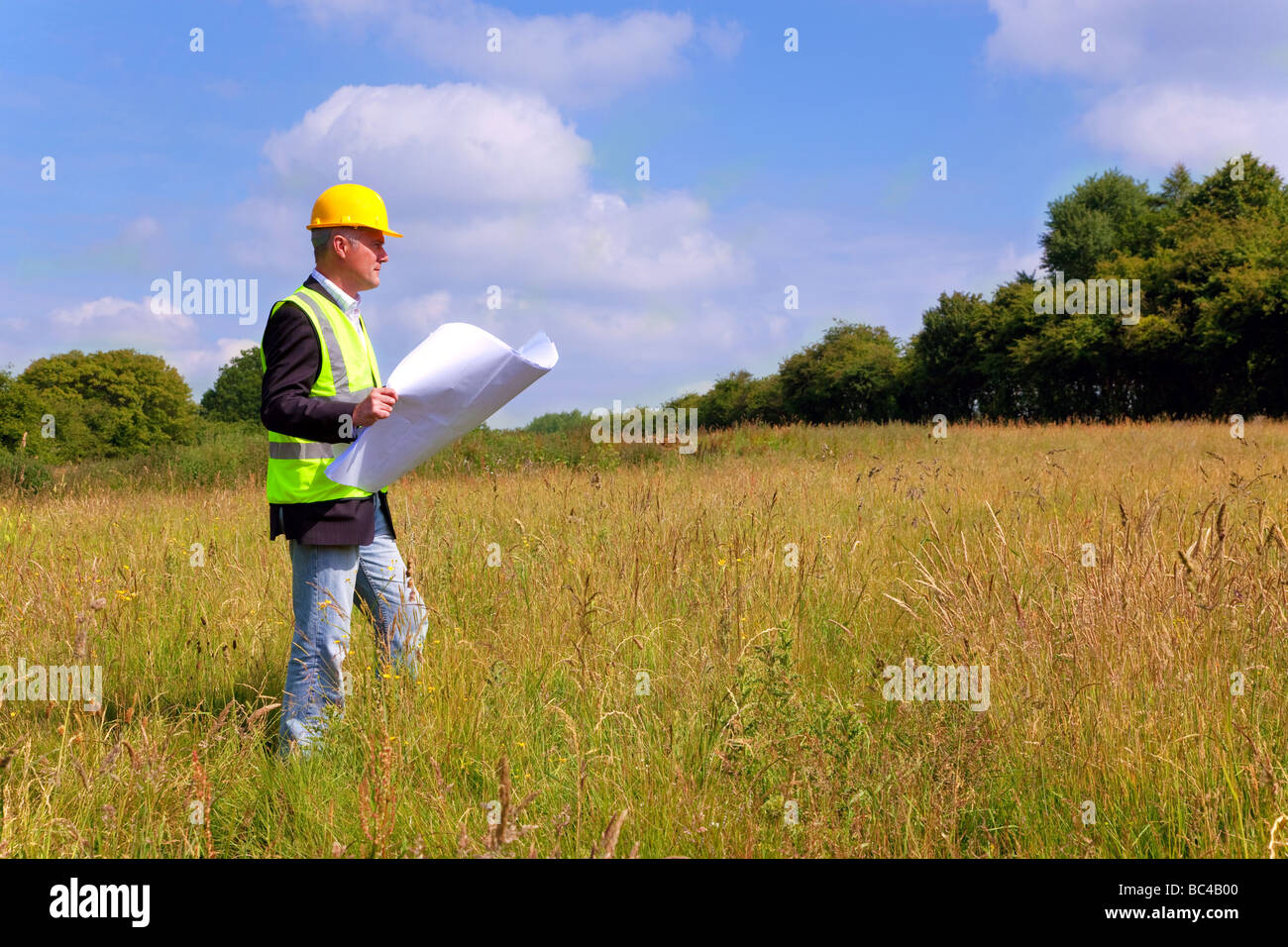 Architect wearing site safety gear and holding plans surveying a new building plot - Stock Image