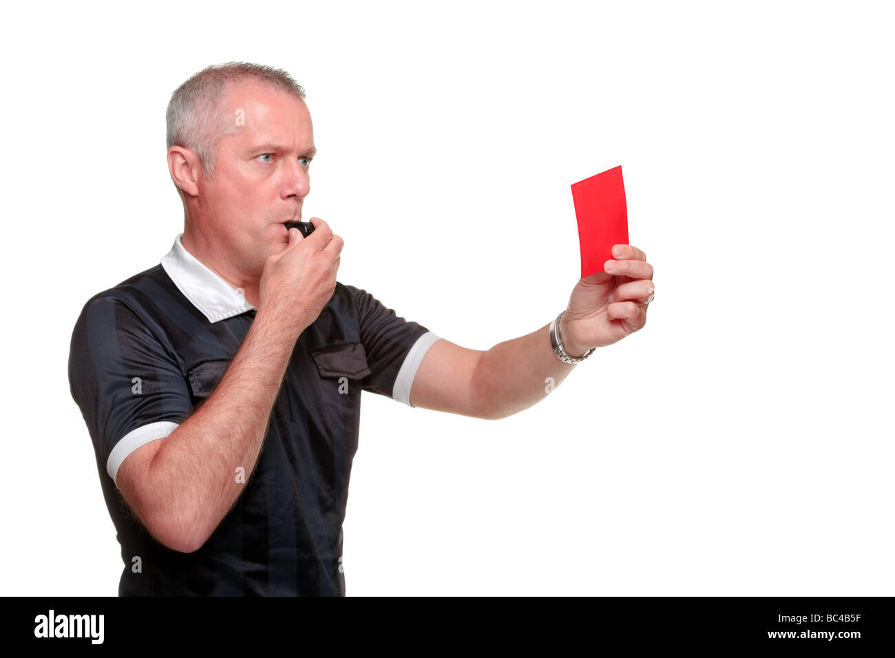 Side profile of a referee showing the red card isolated on a white background - Stock Image