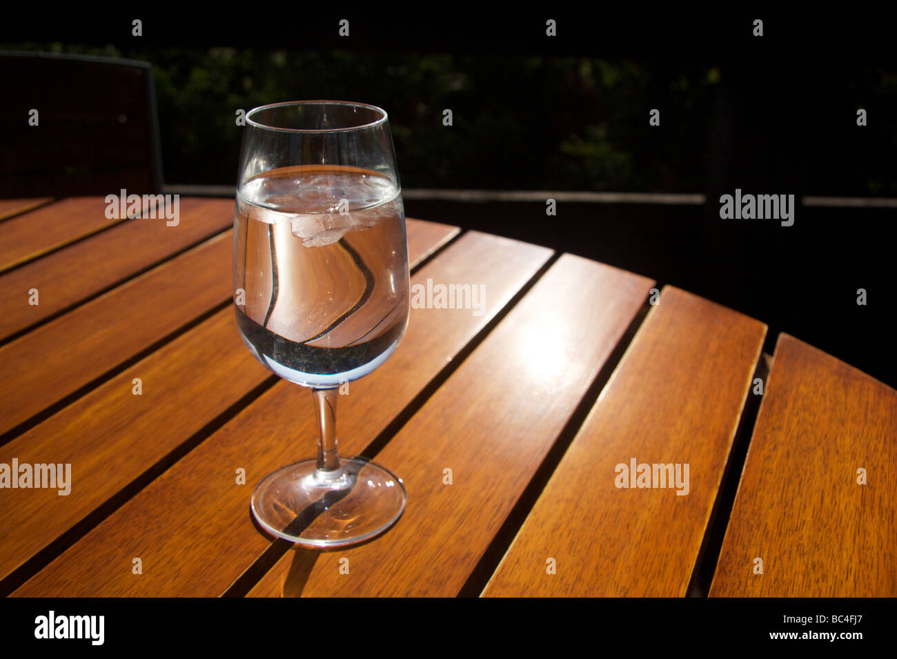 Stemmed glass of water on a wood slat table - Stock Image