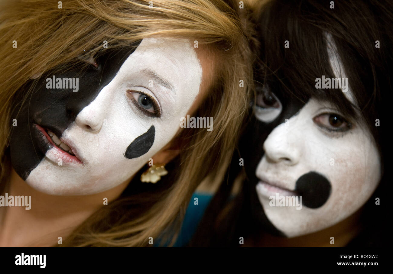 Two teenage girls having had their faces painted in dramatic black and white colours - Stock Image