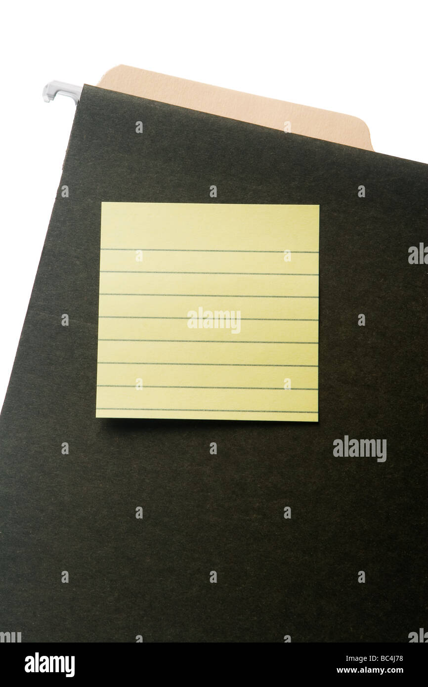 Blank lined post-it note on green hanging file folder. Tab of manila folder inside hanging folder. Isolated on white. - Stock Image