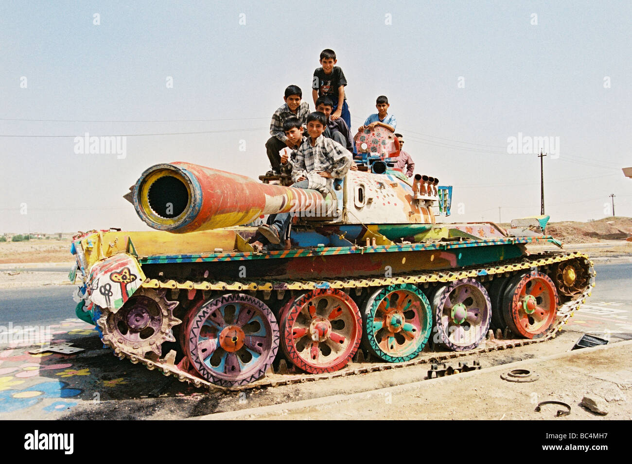 Kurdish children from Kirkuk sit atop a damaged Iraqi T-62 battle tank that is painted and covered in graffiti, - Stock Image