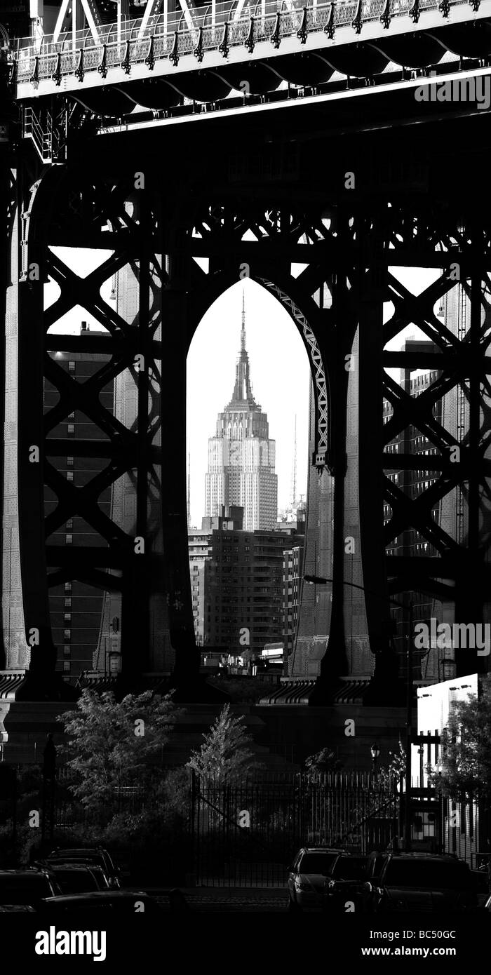 Empire State building seen through the supports of the Manhattan Bridge Stock Photo