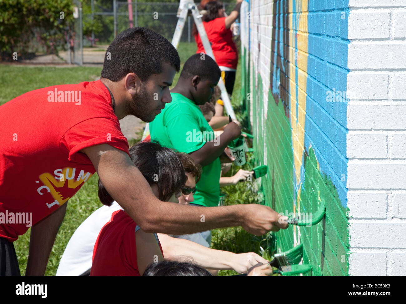 Youth volunteers paint wall in city park - Stock Image