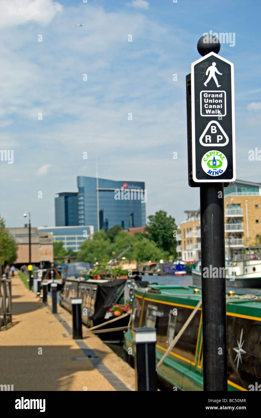 signpost showing routes for grand union canal walk, capital ring, and brent river park footpath, brentford, london, - Stock Image