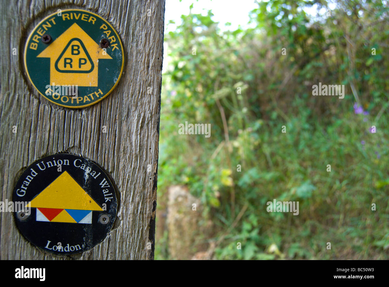 signpost showing directions for the grand union canal walk and the brent river park footpath - Stock Image