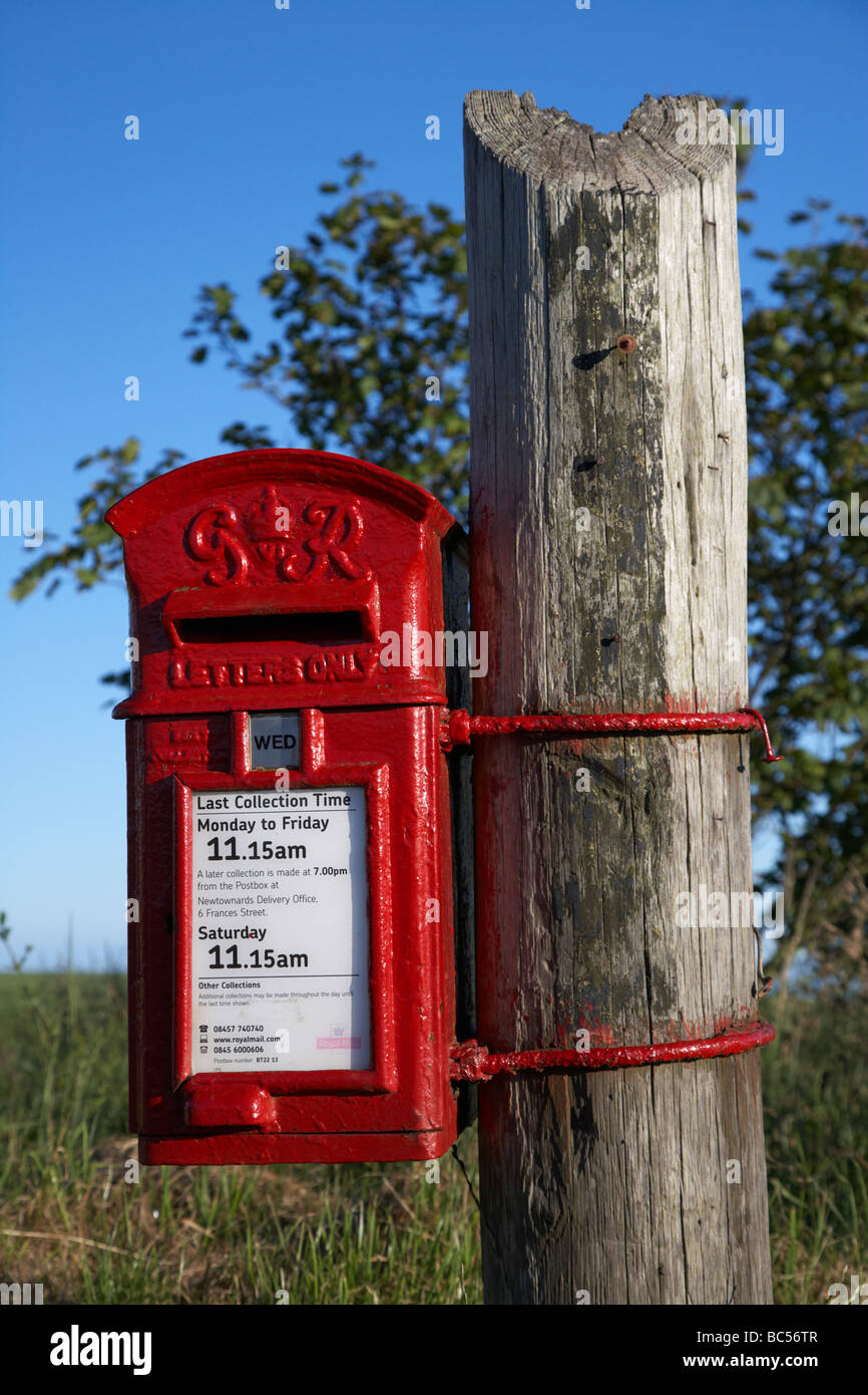 freshly painted red GR post office mail collection lampbox postbox tied to a part telegraph pole in county down Stock Photo