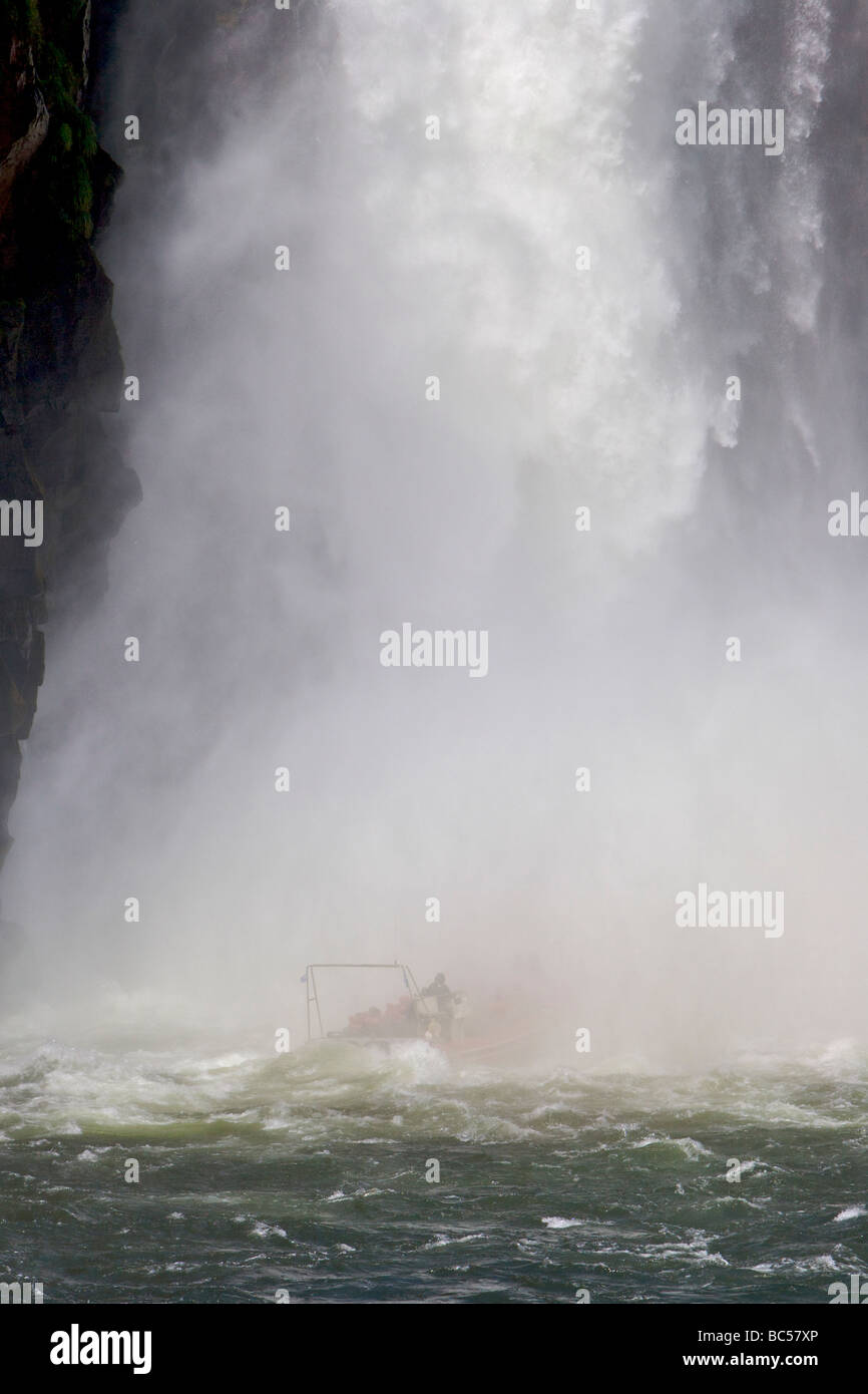 A tour boat with tourists passes under a large waterfall at Iguazu Falls. - Stock Image