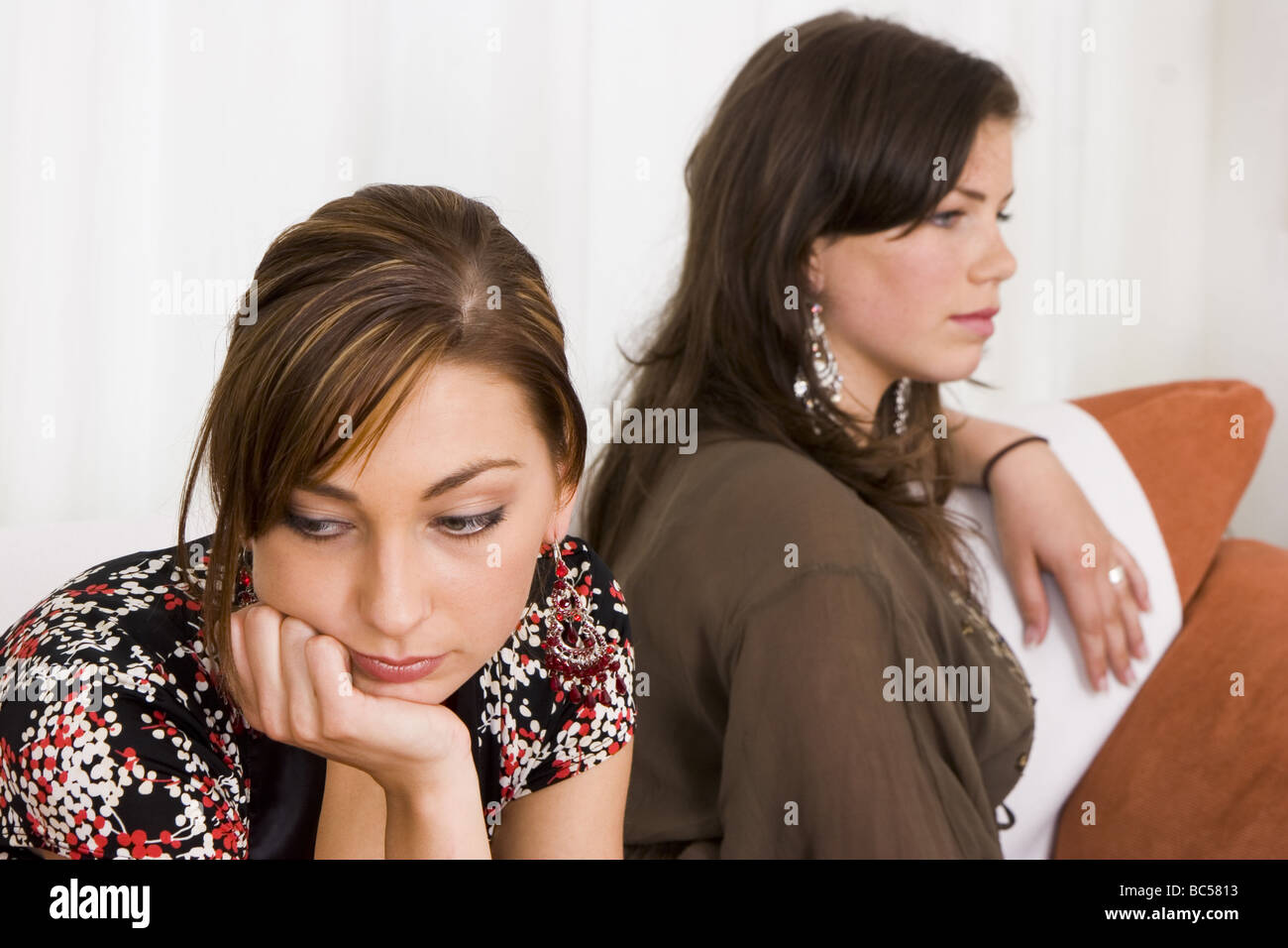Two teenage girls sit silent on sofa, back to back, angry crossed and headstrong with each other, by discord.   - Stock Image