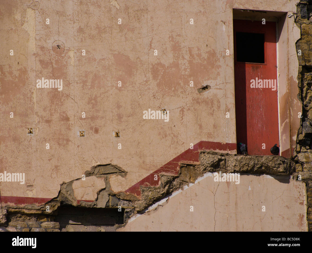 A door and demolished stairway in the wall of the former Singers factory in Frome. - Stock Image
