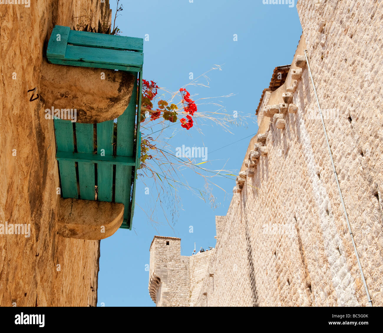 Flower box on a house inside the high city walls of Dubrovnik, Croatia.  Tourists can be seen on the wall. - Stock Image