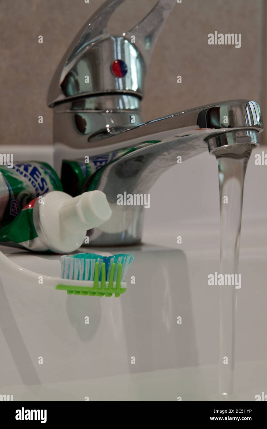 Close up of toothbrush and paste with basin tap - Stock Image