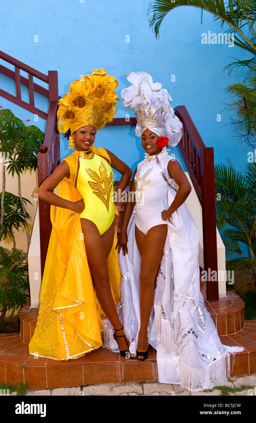 Beautiful dancers in costume against blue wall with headresses in the old colonial city of Trinidad in Cuba Stock Photo