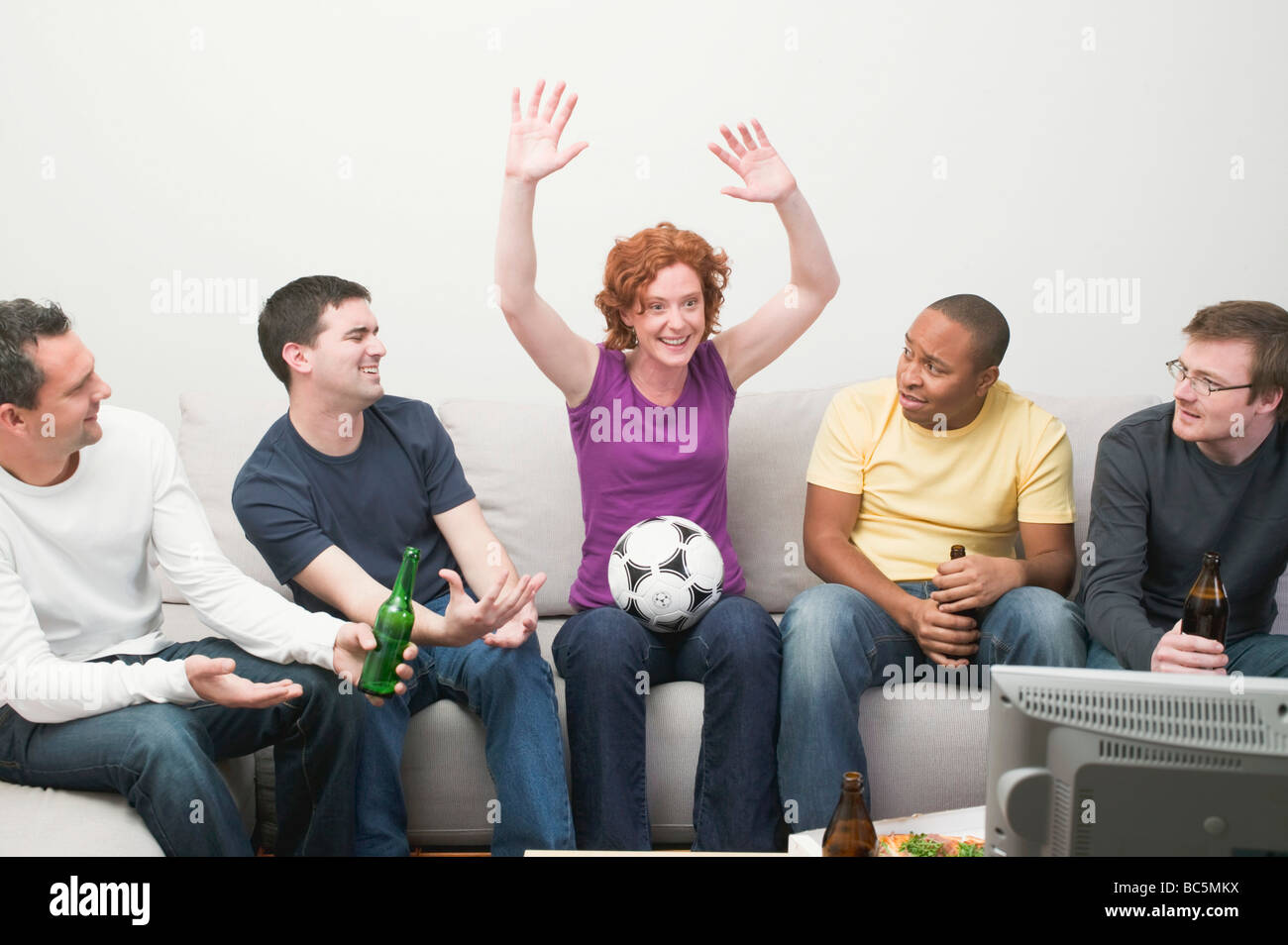Friends with football and beer sitting in front of TV - - Stock Image