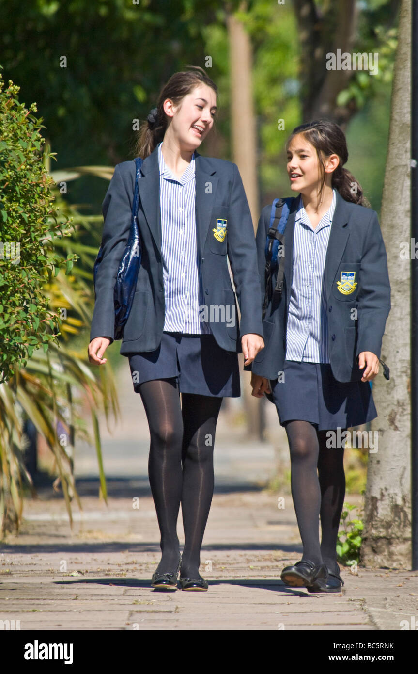 2 young caucasian girls (sisters 12 & 14) smiling and chatting while walking home/to school wearing their uniform. - Stock Image