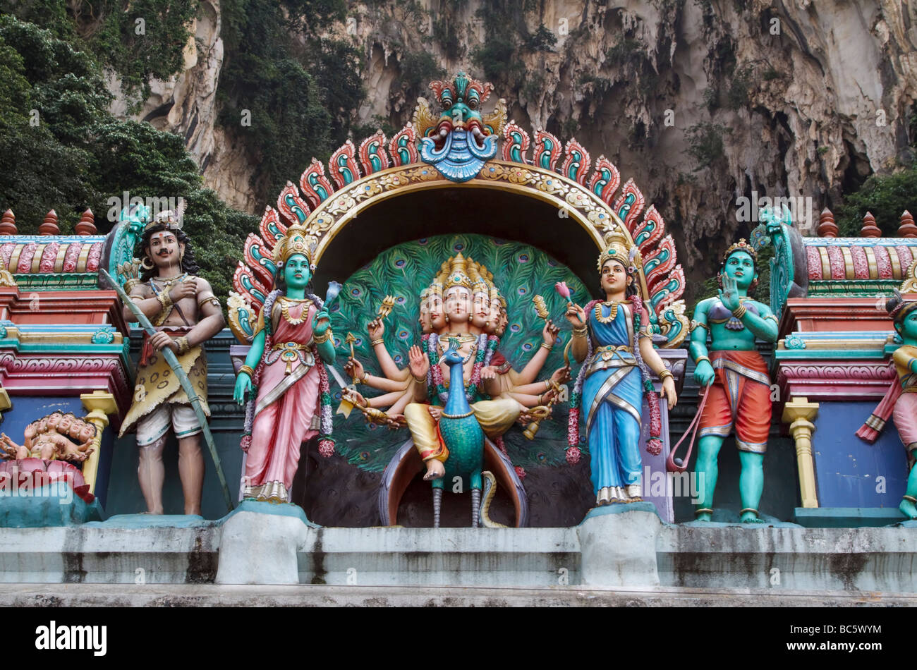 Statues of Lord Murugan and Hindu deities on top of a temple at the base of the steps at Batu Caves, Kuala Lumpur, - Stock Image