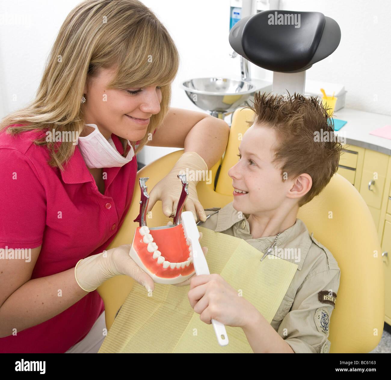 Female dentist showing denture boy - Stock Image