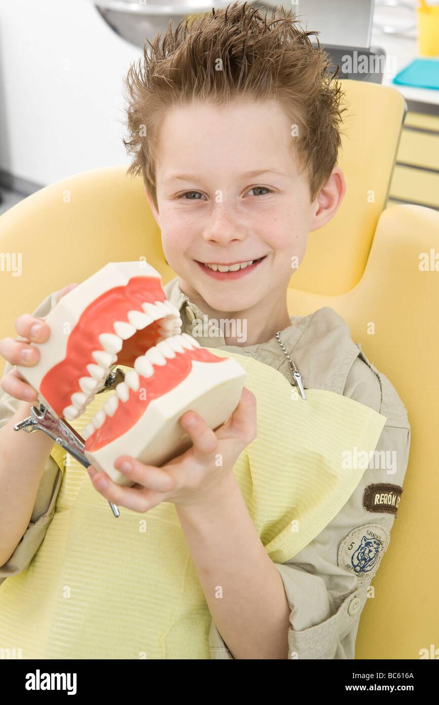 Portrait of boy holding denture - Stock Image