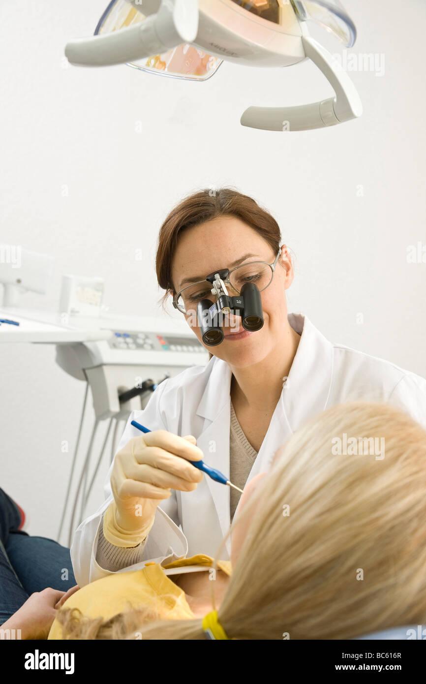 Female dentist examining patient's teeth - Stock Image