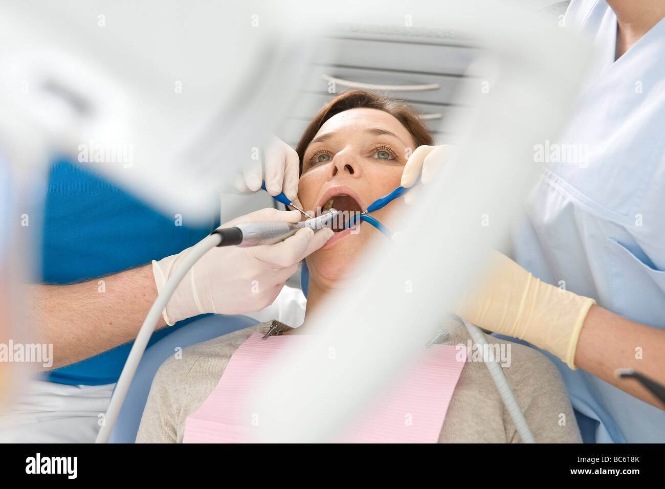 Male dentist and assistant examining patient's teeth - Stock Image