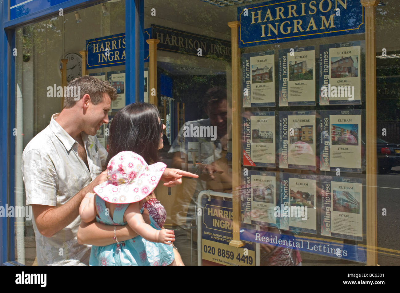 A trendy young couple (late 20's) with their baby looking in an estate agents window for property to let or - Stock Image