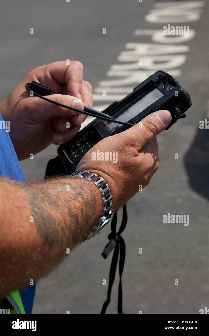 No Parking _Meter attendant issuing ticket using hand held device, Helmsley, North Yorkshire UK - Stock Image