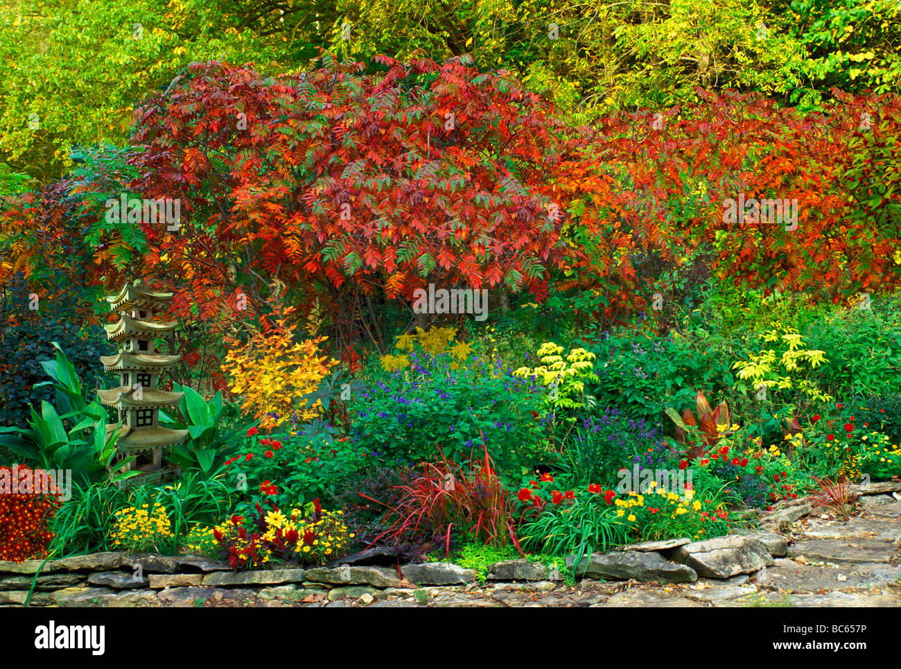 Ornamental Japanese Pagoda Statue Placed In Garden Of Bright Colored  Blooming Plants In A Red And Yellow Garden, Midwest USA