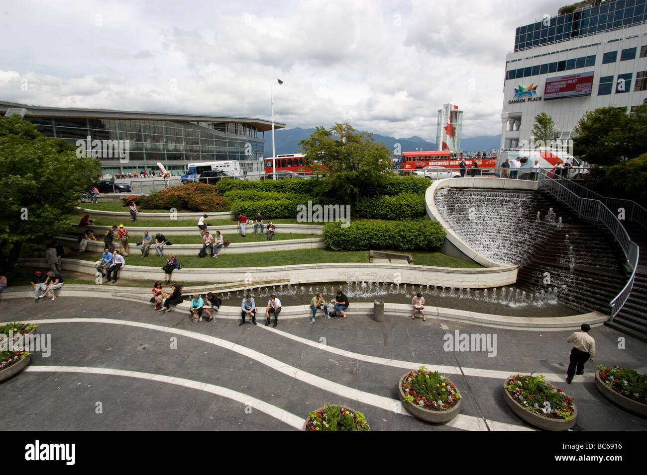 Canada place downtown Vancouver office workers having lunch by fountain outside food hall waterfront centre mall - Stock Image