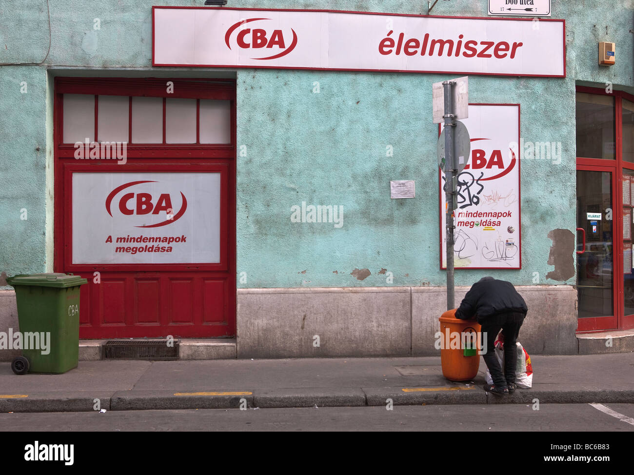 A man rummaging through trash in Budapest, capital of Hungary. - Stock Image