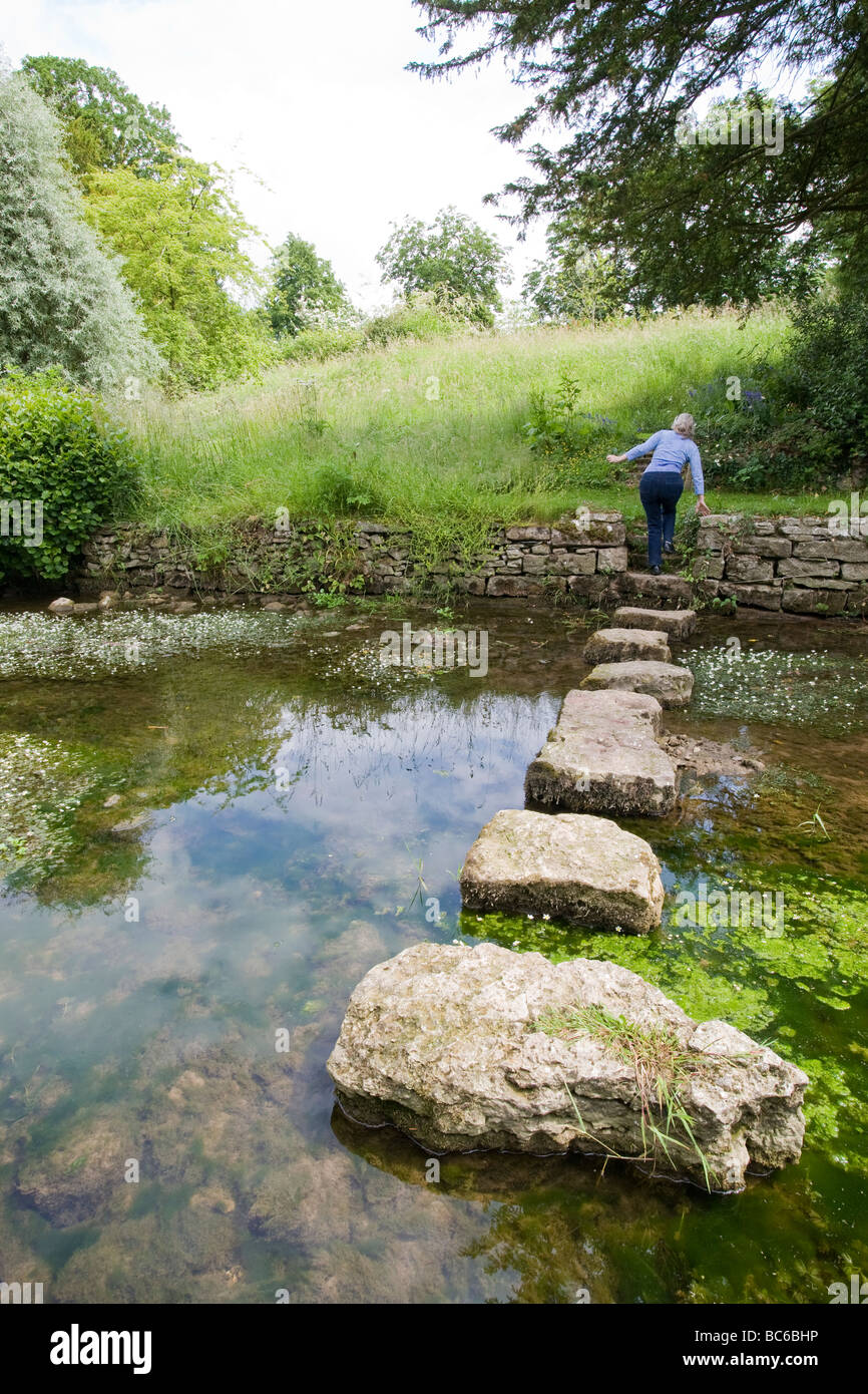 Back view of female at the end of a series of stepping stones over a small stream with grass and tress in distance - Stock Image
