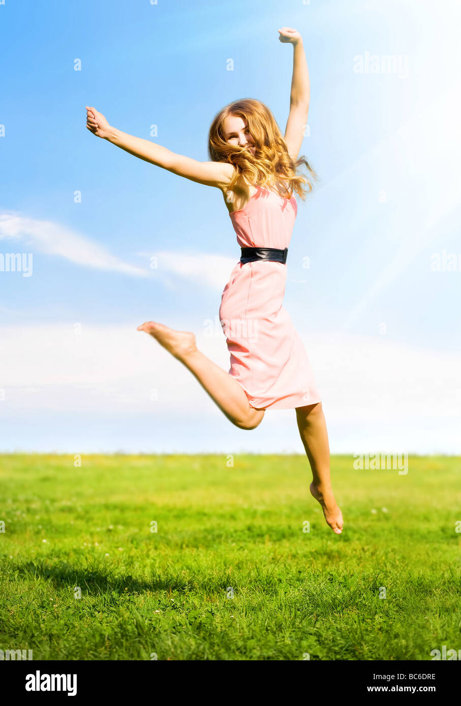 Happy jumping girl on summer field background - Stock Image
