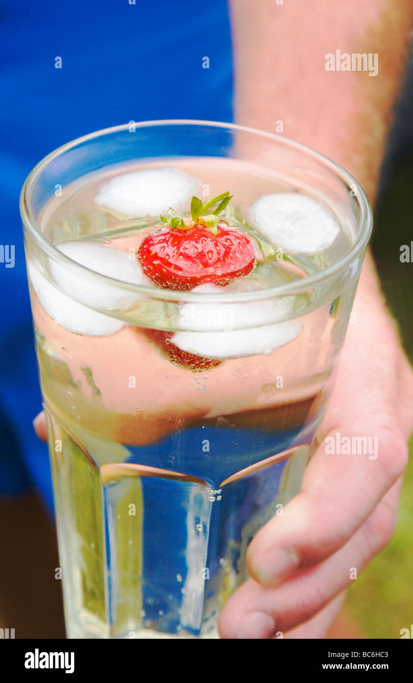 A man holding a long cool drink with ice and a fresh strawberry. Pear cider. UK - Stock Image