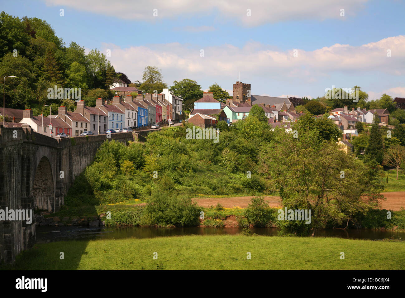 The River Towy flowing under a stone bridge below the hillside town of Llandeilo - Stock Image
