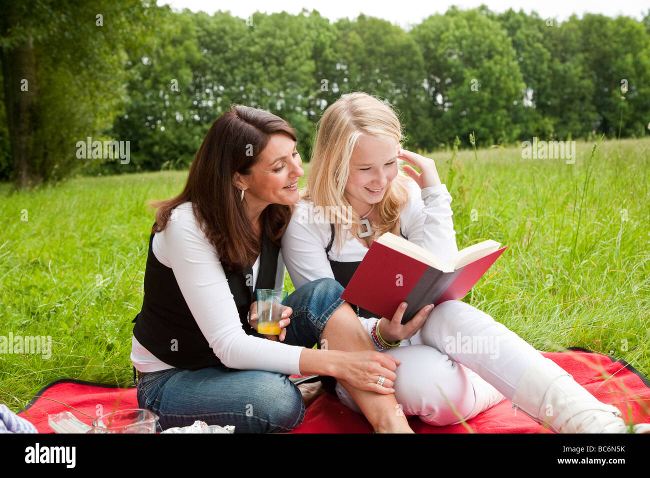 Mother and daughter outdoors on a picnic blanking reading together - Stock Image