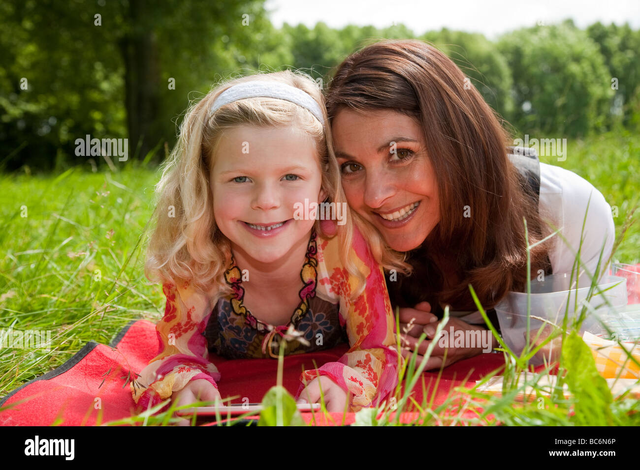 Beautiful mother and daughter together outdoors in the field - Stock Image