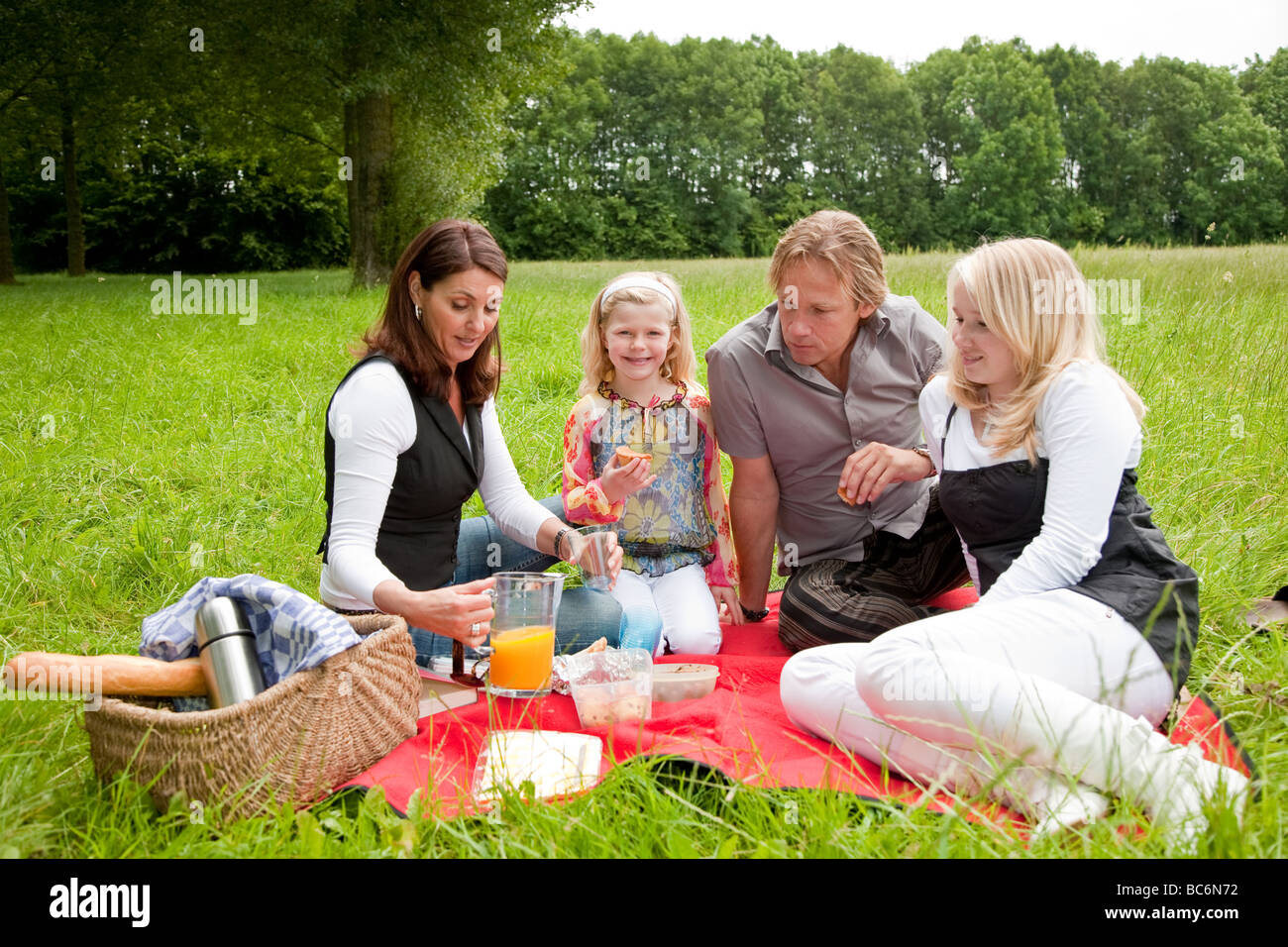 Pretty young family on an outdoors picnic in the field - Stock Image