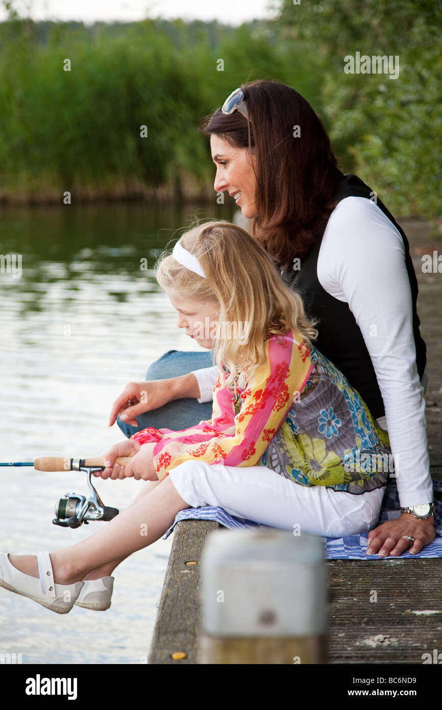 Young girl by the waterside with her mom trying to catch a fish - Stock Image