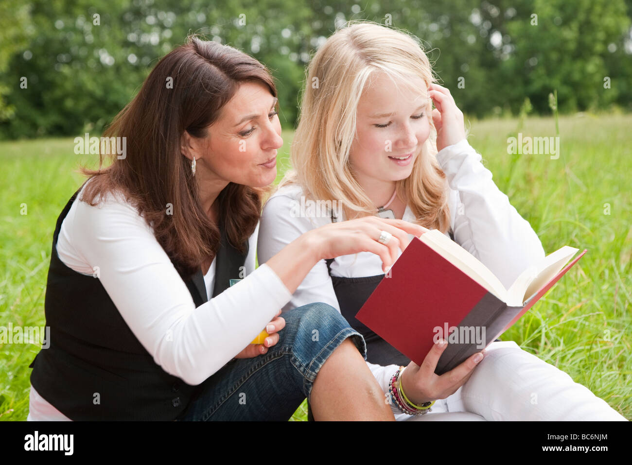 Pretty girl and her mother checking out a book together - Stock Image